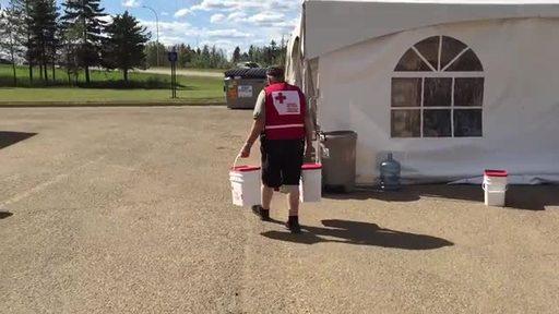 Vidéo : Des bénévoles de la Croix-Rouge canadienne transportent des trousses de nettoyage qui seront distribuées aux sinistrés revenant à Fort McMurray après les feux de forêt de 2016.