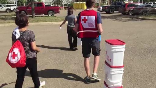 Vidéo :Un bénévole de la Croix-Rouge canadienne aide une résidente de Fort McMurray à transporter sa trousse de nettoyage après les feux de forêt de 2016.