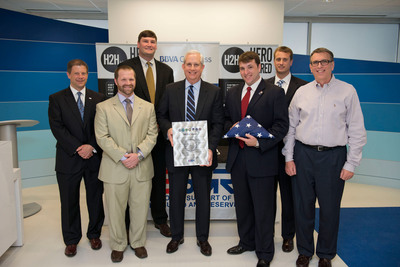 From left to right, BBVA Compass employees Ryan Kraynick, Brett Mixon, Jon Higginbotham, Jim Heslop, Ben Blass, Dwight Julbert and Kelcey Wharton pose with the plaque and flag presented to BBVA Compass by the ESGR.  (PRNewsFoto/BBVA Compass)