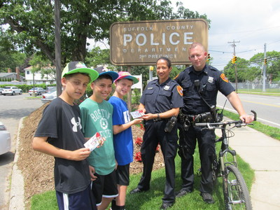The Suffolk County, Long Island, NY, Police Department (SCPD) is among some 700 law-enforcement agencies in the U.S. participating in 7-Eleven, Inc.'s Operation Chill campaign this year. Police patrol personnel ticket youngsters with a free Operation Chill Slurpee(R) coupon for good behavior, belonging to a positive community group or helping others. Pictured here are, from left, Suffolk County youngsters Justin Galluzzo, Anthony Johnson and Vincent Milazzo. Providing them with Operation Chill coupons are SCPD community liaison Claudia Delgado and SCPD 2nd Precinct Officer Thomas Collins of the department's community bike patrol. (PRNewsFoto/7-Eleven, Inc.)