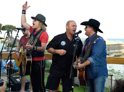 Fan Kenny Waller (center) of Longmont, Colorado signs with Big Kenny and John Rich of Big and Rich at the Holiday Inn Resort on August 23, 2015 in Pensacola, Florida. (Photo by Rick Diamond/Getty Images for Holiday Inn Resort)