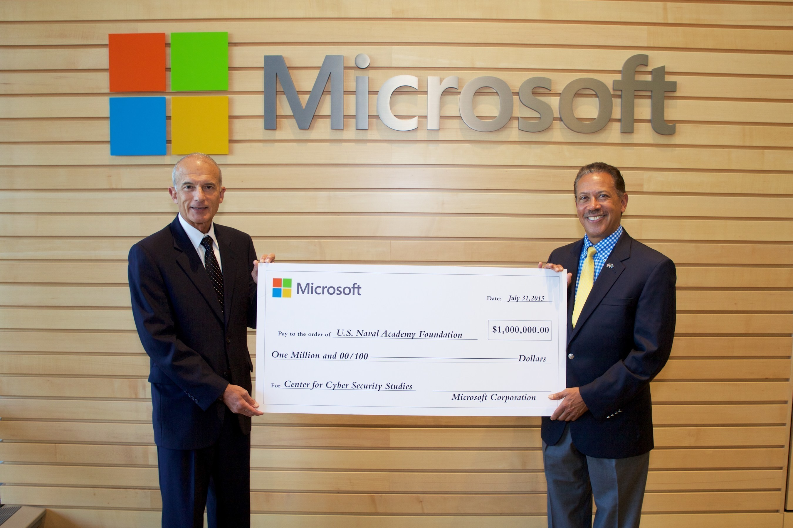 Chris Cortez, vice president, Microsoft Military Affairs, retired U.S. Marine Corps major general and father of Naval Academy graduate Christopher Cortez of the Class of 2002, presents Microsoft's gift to Naval Academy Foundation President and CEO Byron F. Marchant of the Class of 1978.