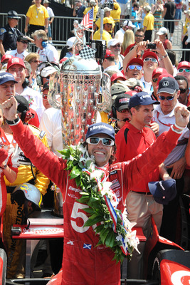 Standing beside the Borg-Warner Trophy(TM) in Victory Lane, Dario Franchitti celebrated his third victory at the 2012 Indianapolis 500. The trophy and Franchitti will join BorgWarner in booth 21635 at the 2012 SEMA Show in Las Vegas.  (PRNewsFoto/BorgWarner Inc.)