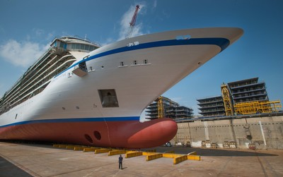 """A shipyard worker is seen next to the hull of the new 930-passenger cruise ship, Viking Star. The ship was """"floated out"""" on Monday, June 23, in a traditional ceremony that took place at Fincantieri's Marghera shipyard outside Venice, Italy. Debuting in spring 2015, Viking Star is the first of three new ships from Viking Ocean Cruises (www.vikingoceancruises.com), with maiden voyages in Scandinavia and the Baltic; and the Western and Eastern Mediterranean. (PRNewsFoto/Viking Cruises)"""