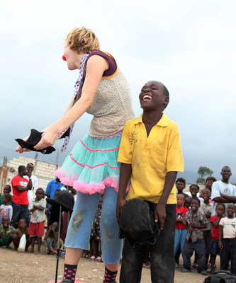 A laughing young boy joins a clown who is performing for a large crowd in Haiti. This project supported earthquake relief.
