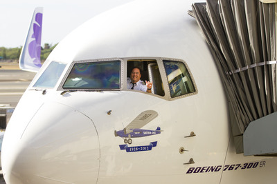 """Capt. Todd Mihara flashes a """"shaka"""" sign, signaling 'all clear' from the cockpit of Hawaiian Airlines' inaugural flight to Brisbane, Australia moments before departure from Honolulu this morning. Below the cockpit window is a commemorative image of the Southern Cross in tribute to the pioneering flight between Hawaii and Brisbane in 1928, piloted by Australian aviators Charles Kingsford Smith and Charles Ulm.  (PRNewsFoto/Hawaiian Airlines)"""