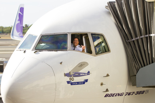"Capt. Todd Mihara flashes a ""shaka"" sign, signaling 'all clear' from the cockpit of Hawaiian Airlines' inaugural flight to Brisbane, Australia moments before departure from Honolulu this morning. Below the cockpit window is a commemorative image of the Southern Cross in tribute to the pioneering flight between Hawaii and Brisbane in 1928, piloted by Australian aviators Charles Kingsford Smith and Charles Ulm.  (PRNewsFoto/Hawaiian Airlines)"