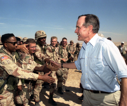 President George H.W. Bush talks with troops in Saudi Arabia, Nov. 22, 1990. Photo: George Bush Presidential ...