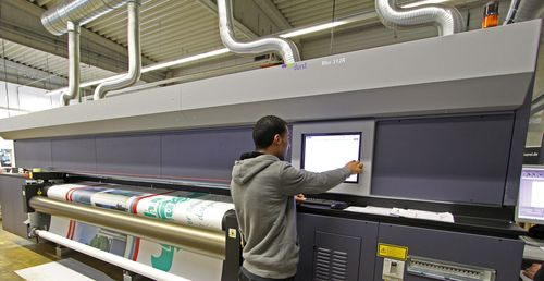 """Ordered today, delivered tomorrow: The new Durst Rho 312R roll-to-roll printer enables customised large-format printing on tarpaulins and mesh in excellent image quality rarely available in the market for outdoor advertising. The use of the printer for large format printing by the Onlineprinters GmbH print service provider enables expressive and colourful advertising messages at the point of sale. Copyright: Onlineprinters GmbH. Editorial use of this picture is free of charge. Please quote the source: """"obs/Onlineprinters GmbH (PRNewsFoto/Onlineprinters GmbH)"""
