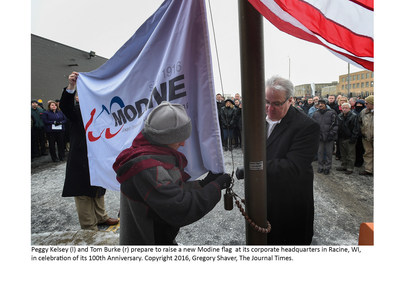 Peggy Kelsey (l) and Tom Burke (r) prepare to raise a new Modine flag at its corporate headquarters in Racine, WI, in celebration of its 100th Anniversary. Copyright 2016, Gregory Shaver, The Journal Times.