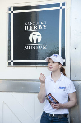 Female jockey Rosie Napravnik takes a second from racing to enjoy new SNICKERS Bites outside of the Kentucky Derby Museum barn in Louisville, Ky. Napravnik, 25, is trying to become the first female jockey to ever win the historic race and should she win, SNICKERS will give away 1 million of their new SNICKERS Bites for free.  (PRNewsFoto/Mars Chocolate North America, Brian Bohannon)