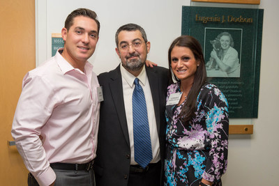 Immune Tolerance Leader Alberto Pugliese, M.D. (center) of the Diabetes Research Institute with John Hughes and Lindsey Inserra-Hughes, in front of a plaque with a photo of the late Eugenia Dodson.  Dr. Pugliese's specialty was highlighted throughout the day during the Lindsey Inserra-Hughes Immune Tolerance Seminar Series and the presentation of the J. Enloe and Eugenia J. Dodson Chair in Diabetes Research, which was held at the Diabetes Research Institute at the University of Miami Leonard M. Miller School of Medicine.