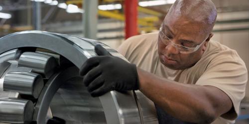 Timken associate Patrick Garner inspects a spherical roller bearing. (PRNewsFoto/The Timken Company) ...
