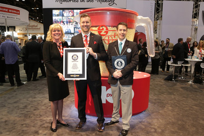 From left to right, Kris Malkoski, North American president of World Kitchen, and Mike Scheffki, Pyrex brand lead, with Philip Robertson, Guinness World Record adjudicator, pose in front of the World's Largest Measuring Cup created to celebrate the Pyrex 100th anniversary at the International Home and Housewares Show in Chicago on Sunday, March 8, 2015. (Jean-Marc Giboux/AP Images for Pyrex Brand)