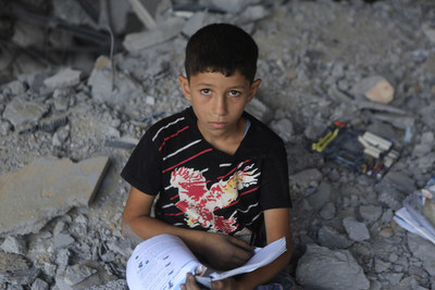 Rayan*, 13, in the rubble of his former school in the Gaza Strip. (* indicates that the name has been changed to protect identity. This must be reflected in all usage). Photo by Anas Baba/Save the Children.