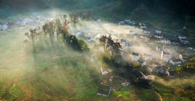 Morning mist draping Shicheng Village in Wuyuan County