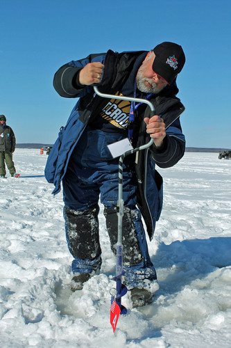 Team USA angler, Myron Gilbert, uses a hand auger to drill through 20 inches of ice at the 2013 World Ice Fishing Championship on the Big Eau Pleine Reservoir near Wausau, Wisconsin. (PRNewsFoto/Recreational Boating & Fishing Foundation, Take Me Fishing(TM)) (PRNewsFoto/RECREATIONAL BOATING & FISHING..)