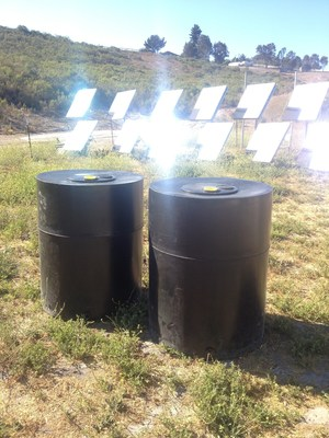 LightManufacturing Sustainably Molded Water Tanks stand in front of Array of H1 Heliostats - each heliostat delivers over 1000 watts of concentrated solar thermal energy for zero carbon plastic molding.