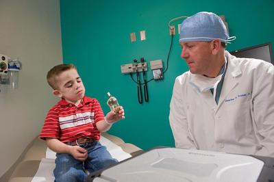 Former Berlin Heart patient, Brady Burch, shares a moment with Dr. Charles D. Fraser, Jr., surgeon-in-chief at Texas Children's Hospital in Houston. Fraser shows Burch the small heart pump that Fraser implanted to save Burch's life when he was born with a severe heart defect.