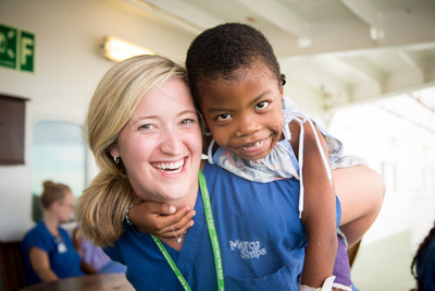 Mercy Ships volunteer nurse Meredith Herring plays with a patient onboard the hospital ship using EMC communications and content services - Africa Mercy in Madagascar, Africa. (C)Mercy Ships/Katie Keegan