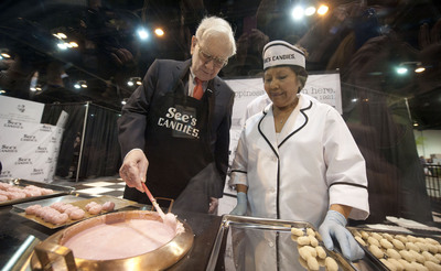 Candy for Breakfast?: Prior to the start of Berkshire Hathaway's 2013 annual meeting, Chairman & CEO Warren E. Buffett makes some coconut bon bon treats in the See's Candies exhibit. With him is Victoria Melena, a 40-year-employee of See's Candies. Buffett acquired See's in 1972.(PRNewsFoto/See's Candies)