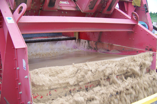 This equipment is removing excess moisture from clean sand using a dewatering screen. The screen, which vibrates and shakes out the sand, separates the water for reuse in the washing process. The dewatered sand, with about 15% moisture, goes to a stockpile. As the stockpile sand sits and weeps, drain tiles under the stockpile allow even more water to be recaptured and put back into the washing process. (PRNewsFoto/Fairmount Minerals)