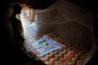 Mother watches while baby sleeps under new mosquito bed-net.