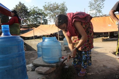 An earthquake survivor washes her hands using clean water provided by WaterAid. Handwashing with soap is key to preventing the spread of diseases such as cholera.