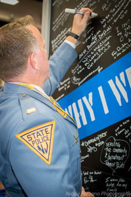 Lt. Craig Costello from New Jersey State Police signs Vigilant's Why I Wear the Badge wall at IACP 2016.