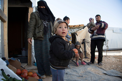 Dina *, left, lives in a caravan in Za'atari refugee camp in Jordan with her husband and three children, ages 3, 2 and 18-months old. Her husband buys vegetables and sells them on to their neighbors. The family also dries flat bread in the sun and sells the hardened crumbs to farmers as bird food (* name changed to protect identity). Rosie Thompson/Save the Children.  (PRNewsFoto/Save the Children)
