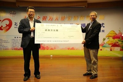 Dr. Tzu-Yin Chiu, Chief Executive Officer and Executive Director of SMIC (right) presents a cheque to Jing Dunquan, Vice Chairman of China Soong Ching Ling Foundation (left) worth 2 million yuan.