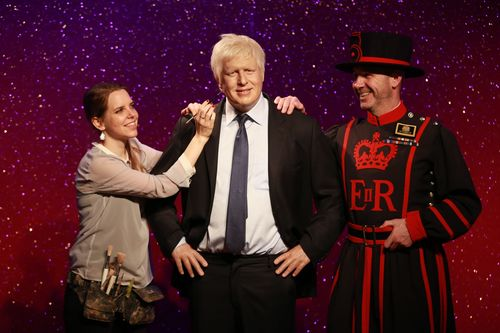 """Rebecca Holmes, colouring artist at Madame Tussauds London and Barney Chandler, Yeoman of the Guard (""""Beefeater""""), attend the launch of VisitLondon.com's new campaign along with a wax figure of Mayor of London Boris Johnson at Madame Tussauds London. The London Story is a celebration of the capital backed by the Mayor of London, and is a series of films compiled by VisitLondon.com, the official city guide, of people who live and work in the capital, as well as famous Londoners, talking about what they love about living in the capital. (PRNewsFoto/London & Partners)"""