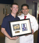 On the one-year anniversary of his donor heart transplant, Jordan Merecka presents his surgeon and friend Dr. David S.L. Morales with a display case holding Jordan's SynCardia Total Artificial Heart and a picture of Jordan's photo on the Times Square JumboTron in New York City. (PRNewsFoto/SynCardia Systems, Inc.)