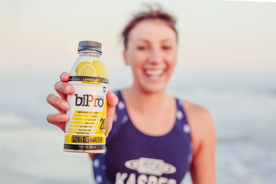 Kirsten Kasper grabbing a bottle of BiPro Protein Water after an open water swimming workout.