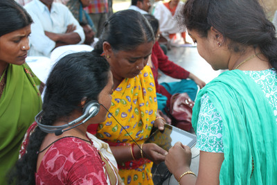 Safe Water Network's station operator helps consumers in the village of Thodellagudem experience Tablet messaging. Developed with the support of The Merck Foundation and Dialogue Factory, we are taking a high-tech approach to building demand for safe water in rural areas of India.  (PRNewsFoto/Safe Water Network)