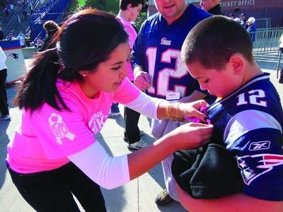 ZTA volunteer pinning a breast cancer awareness ribbon on a NFL fan. (PRNewsFoto/Zeta Tau Alpha Foundation)