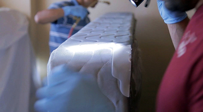 During the IR4 field study, entomologists conducting inspection and applying EcoRaider directly onto a mattress in an infested housing apartment. (PRNewsFoto/Reneotech Inc.) (PRNewsFoto/Reneotech Inc_)