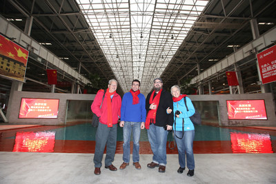 Four of SANY's global spokespeople posing in SANY's No. 18 intelligent manufacturing factory, during their industrial tour in China