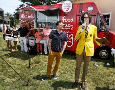 Dan Rollman, CEO of RecordSetter, joined by Chef Rocco DiSpirito, center, announces that Chef Michael's food for dogs has set a RecordSetter World Record by hosting 224 people at the Largest Dog-Friendly Communal Dining Event, Saturday, June 29, 2013, in Bridgehampton, N.Y. (John Minchillo/AP Images for Chef Michael's).