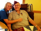 Hospice of the Western Reserve nurse, Amber Varner, gives a hug to World War II veteran and Purple Heart recipient Frank Banach. The handmade quilt in Banach's lap is the gift of a hospice volunteer.