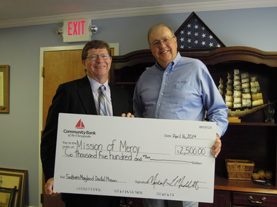 From left to right: Community Bank Executive Chairman of the Board Michael Middleton presents the donation check for Southern Maryland Mission of Mercy to Dr. Garner Morgan.
