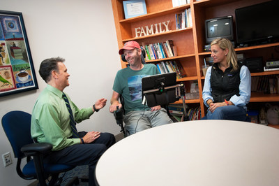 John Costello, Director of the Augmentative Communications Program at Boston Children's Hospital works with ALS patient Todd Quinn on his message banking phrases as Todd's wife Cat looks on.