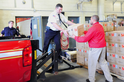 Allentown Assistant Fire Chief Christopher Kiskeravage and State Farm Community Specialist Dwayne Redd load boxes of Canary home security devices onto a fire truck at the national kick-off for Protect the Protectors.
