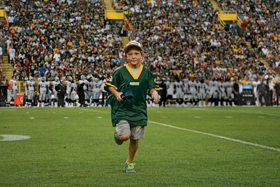 Kick-Off Kid trots off the field at Green Bay Packers home game.