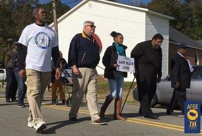 North Carolina native J. David Cox Sr., second from left, who heads the nation's largest federal employee union, the American Federation of Government Employees, marches to the polls with voters from Windsor, N.C., on Nov. 4 in an outreach effort being led by the Rev. William J. Barber, second from right, civil rights leader and member of the NAACP's national board.