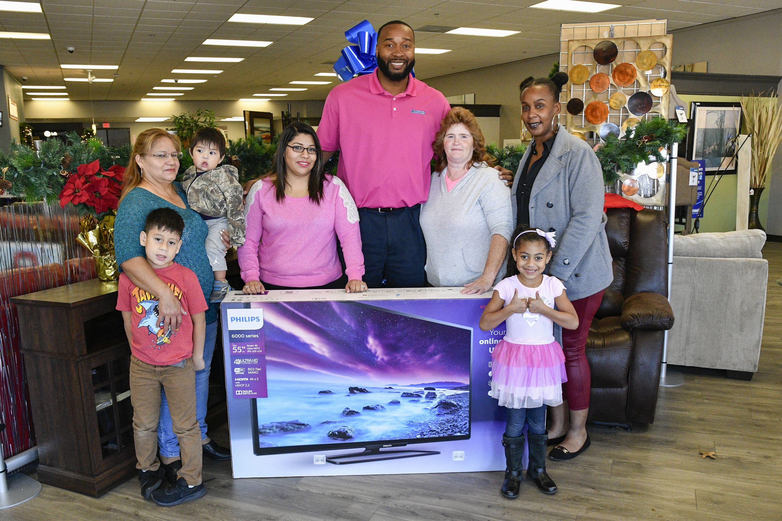 "IMAGE DISTRIBUTED FOR AARON'S, INC - Aaron's regional manager Tyrone Washington, center, surprised loyal customers (L - R) Aurora Moreno, her daughter and grandchildren, Melissa Neese and Salina Arnold with free 55"" Phillips Smart 4K UHD LED TVs at an Aaron's store on Monday, Nov. 21, 2016, in Atlanta, Ga. Aaron's kicked off a week-long Black Friday celebration today and also surprised loyal customers in Jacksonville, Fla., Memphis, Tenn. and Nashville, Tenn. with free 55"" Phillips TVs. (John Amis/AP Images for Aaron's, Inc.)"