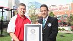 Guinness World Records adjudicator Philip Robertson presents Nathan's Famous representative Chris Madigan with Official World Records Title Certificate.