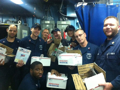 U.S. Navy sailors open care packages from Operation Gratitude.  (PRNewsFoto/SmartphoneTradeIn.com)