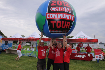 2012 Cabot Community Tour Bike Riders Bob Spiegelman (left), Myron and Kathy Skott (right) and Roberta MacDonald, Cabot Creamery Cooperative Senior Vice President of Marketing (sunglasses), hoist a giant globe above their heads in Celebration of the conclusion of the 2012 Cabot Community Tour.  MacDonald joined the riders during the final 300 miles of their 2,300-mile journey that began May 12 in Miami, FL and ended on July 7 in Portland Maine.  (PRNewsFoto/Cabot Creamery Cooperative)