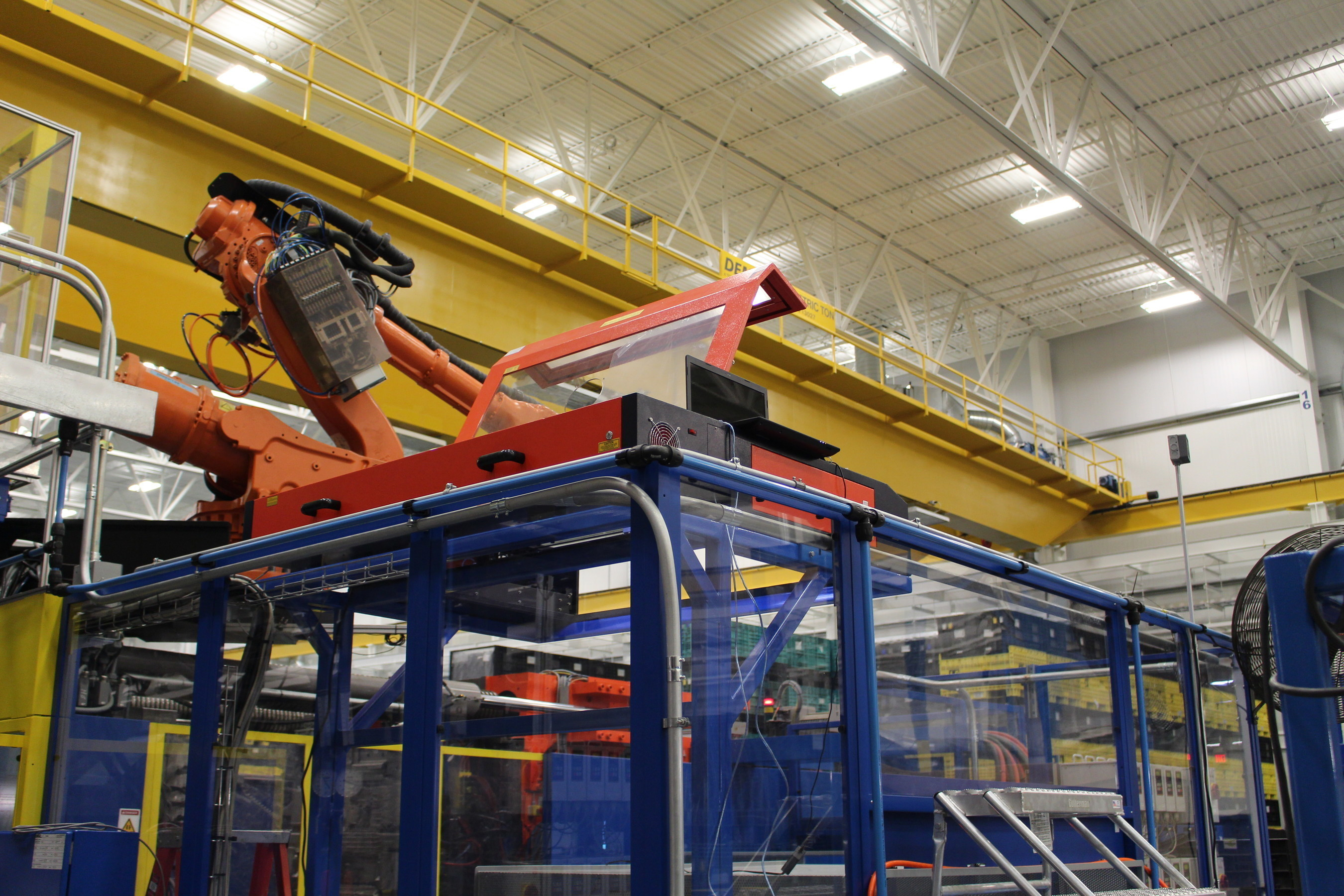 Roechling Automotive USA integrated AP LAZER with a radial arm robot to cut excess off of large high performance plastic auto parts.